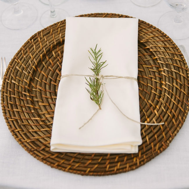 The tables were set with ivory linens tied with a fresh sprig of pine for a rustic look that complemented the rattan wicker chargers.