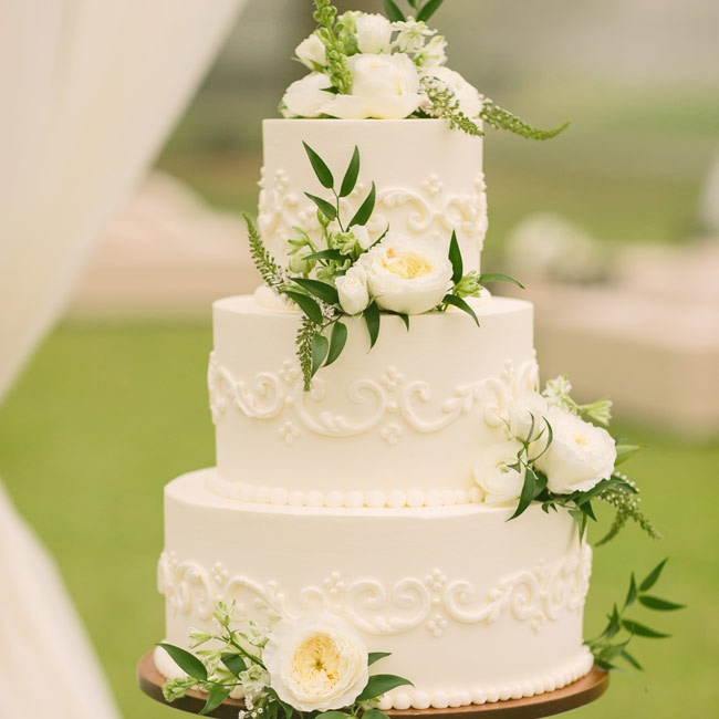 Bunches of ivory peonies and astilbe adorned the Kyla and Drew's elegant buttercream wedding cake.