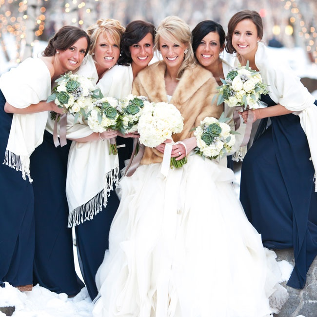 The bridesmaids accessorized their navy Bill Levkoff gowns with matching white wraps.