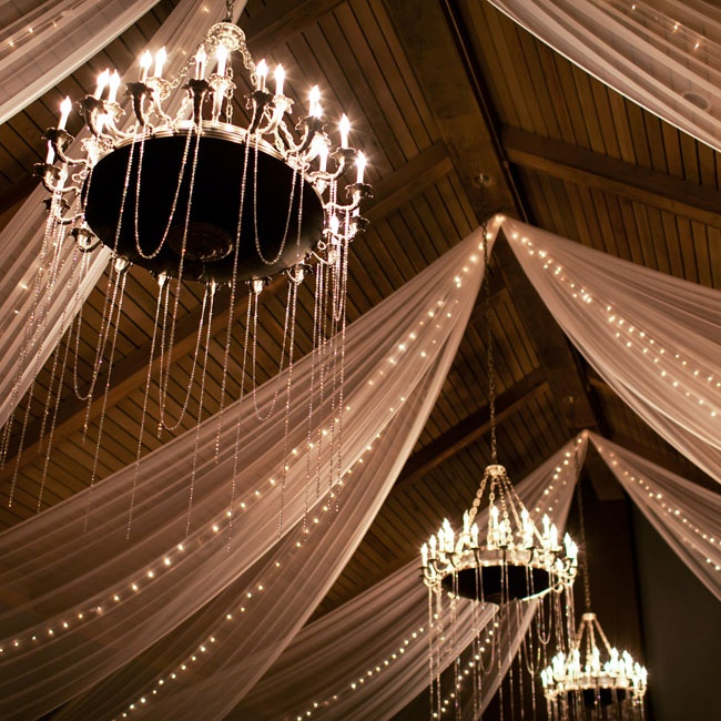 Glittering chandeliers and draped fabric along with strings of light hanging from the ceiling added a drama to the indoor reception.