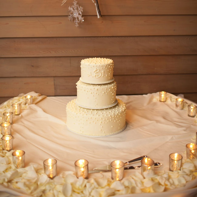 Buttercream dots and a simple monogram adorned the white three tier cake.