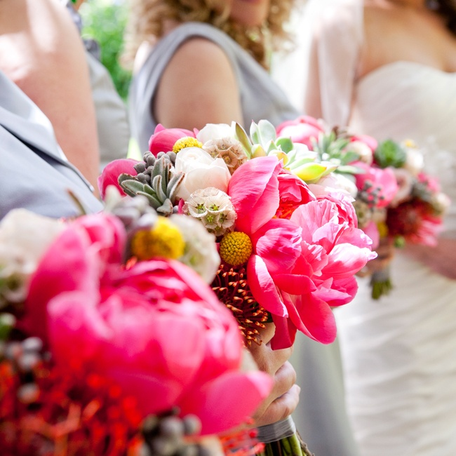 The bridesmaids carried rustic bouquets full of flowers in brilliant shades of pink, yellow and green. Scabiosa, billy balls and succulents added a layer of texture to the softer feel of the bouquet's roses and tulips.