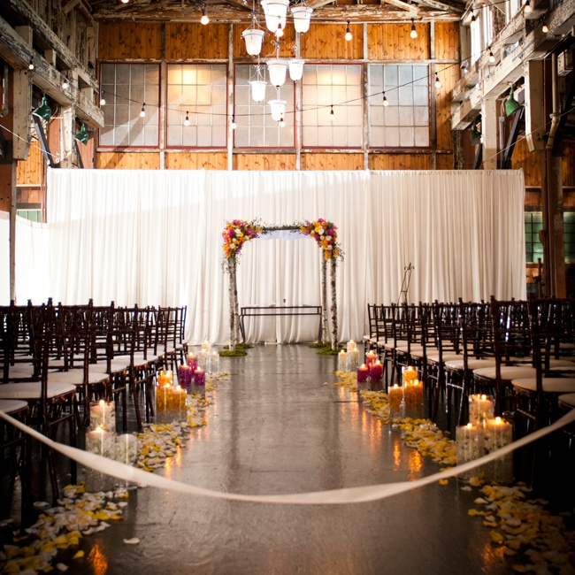 Bari and Matt held their ceremony at Sodo Park in Seattle's historic district. The venue featured a fusion of rustic and modern design elements, which paired with  romantic candlelight, scattered rose petals and a birch wedding Huppah created an elegant, romantic ambiance.