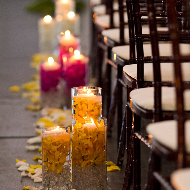 Floating candles set in cylinder vases full of bright orchids gave a modern edge to the romantic decor, while emitting a warm glow for added ambient charm.