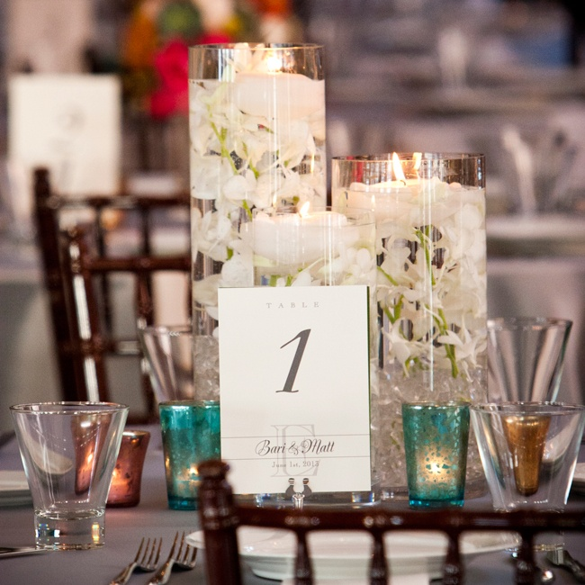 Modern cylinder vases of various sizes filled with white orchids and floating candles topped the reception tables. Smaller votive candles in colored candle holders added a pop of color to the tablescape.