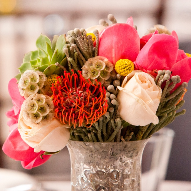 Distressed pewter vases filled with bright eclectic bouquets of tulips, succulents, pincushion flowers, scabiosas, roses and billy balls served as centerpieces for some of the reception's tables.