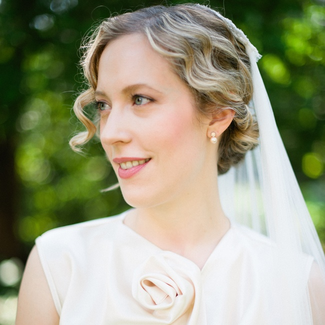 Soft finger waves gathered into a low chignon complemented the vintage-inspired look of Hilary's gown. She completed the look with subtle natural makeup.