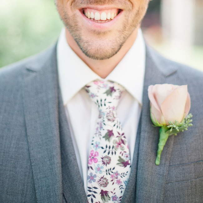 The UK based couple incorporated the signature floral motifs of Liberty of London into many of their weddings details from table runner to Edward's fun floral tie made from the print house's Edenham L Tana Lawn print. He polished off the look with a peach colored rose and eucalyptus berry boutonniere.