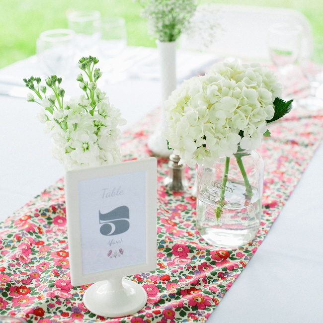The couple decorated their reception tables with table runners made from Liberty of London fabric, adding a pop of color to the tablescapes. Bunches of white hydrangeas and snapdragons in a mismatched array of vases lent a rustic element to the decor.