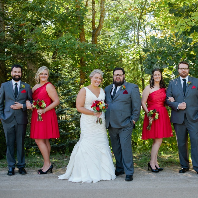 The bridesmaid wore short one-shoulder dresses that matched the affair's red color palette. Mike's groomsmen wore gray suits and skinny black ties. Red pocket squares complemented the red of the girl's dresses.