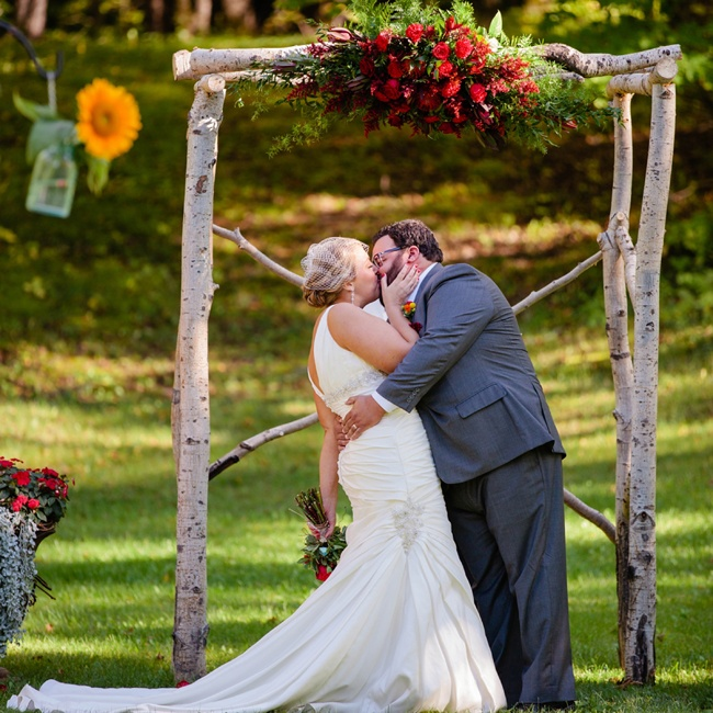 The couple incorporated whimsical woodland elements into the day's decor, such as this birch wedding arch, which they decorated with bright red flowers and greenery.
