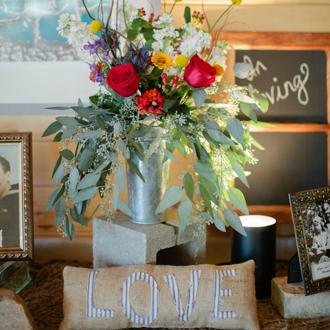 Distressed metal vases added a rustic flair to the reception floral arrangements, which were filled with a colorful assortment of roses, billy balls, snapdragons and a cascade of seeded eucalyptus.