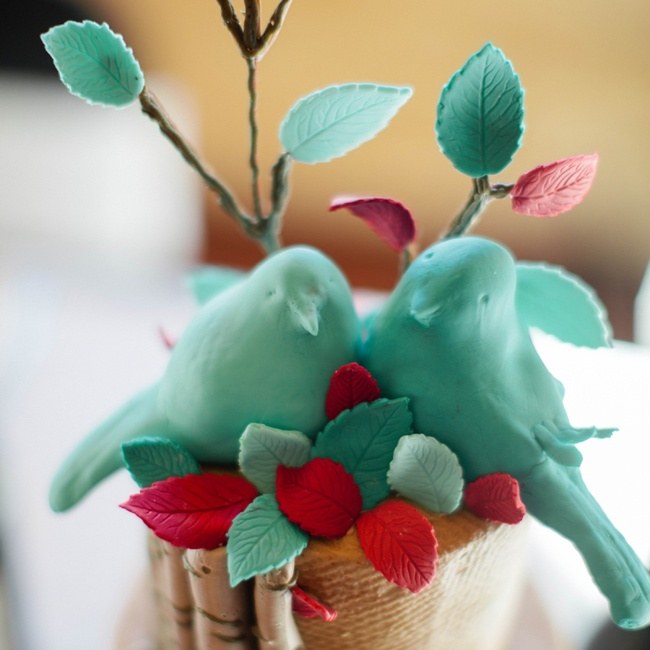 Two turquoise lovebirds surrounded by fondant leaves and branches topped the couple's woodland-inspired cake.