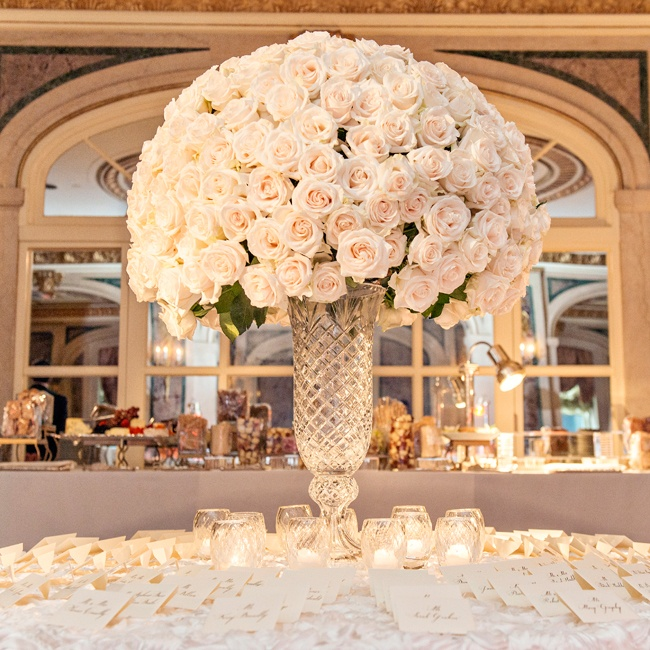 Escort cards surrounded the cocktail hour's focal point, a dramatic dome-shaped arrangement of over 250 ivory roses displayed in a stunning crystal vase.