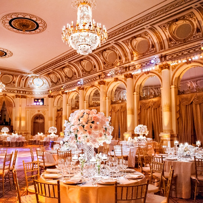An ivory and pale blush floral color palette complemented the venue's opulent gold accents and transformed the dramatic venue into a feminine affair.