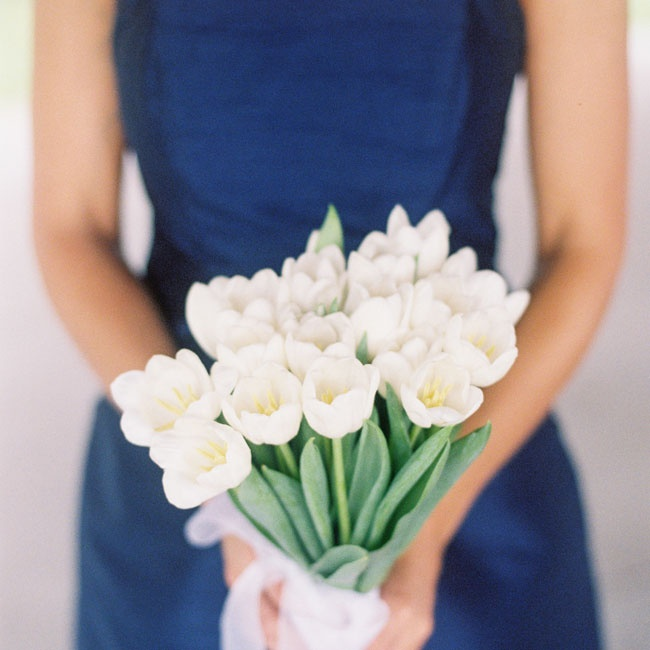 The bridesmaid carried handmade arrangements of opened white tulips.