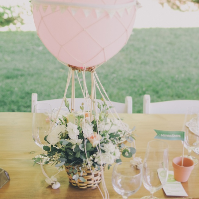 The hot air balloon inspired centerpieces were one of the bride's favorite wedding details. The romantic pastel floral arrangements, which resembled Zurry's bouquet, were all locally sourced and created by Coriander Girl. Zurry and her bridesmaids made the nets for the balloons while Brendan sewed the mini bunting flags that went around the balloon ...