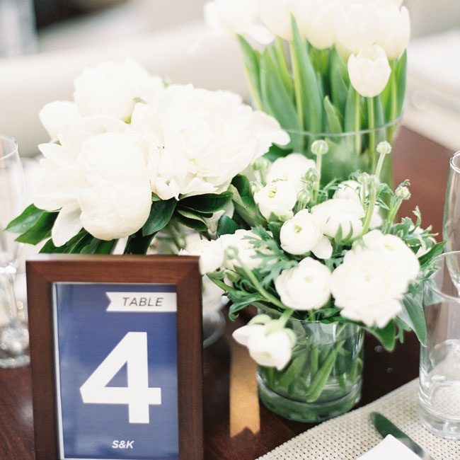 Clusters of simple white flowers and dark framed table numbers added a modern flair to the nautical tablescapes.