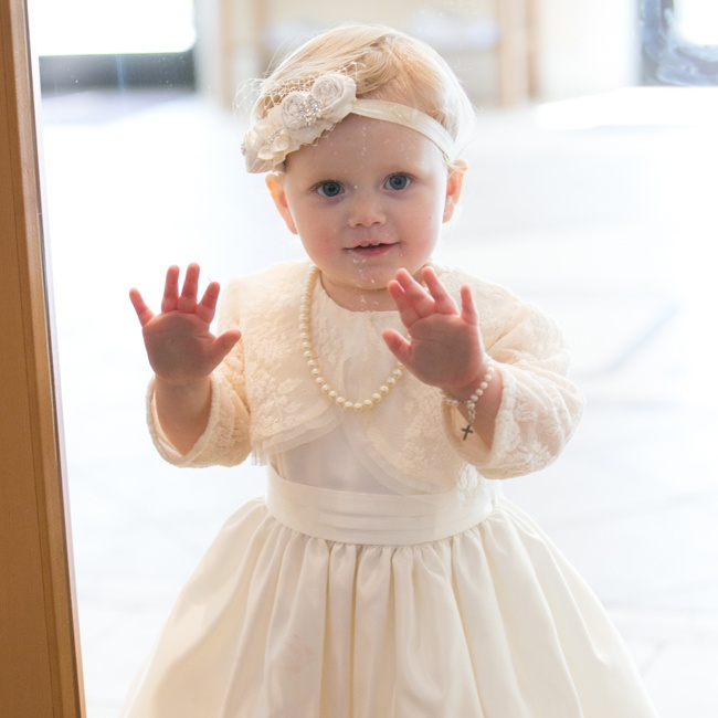 This young relative of the bride and groom wore an adorable white dress and accessorized with pearls and a birdcage veil.