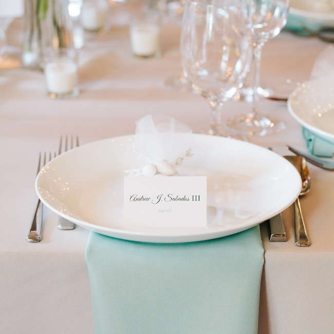 Seats were set with mint linens, and ivory china and placed on a neutral tablecloth.