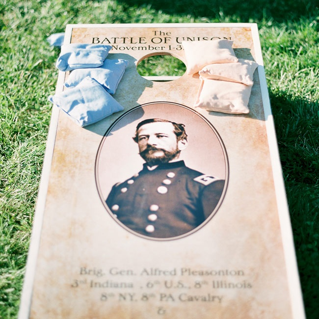 "The bride's father had this vintage-inspired ""Battle of the Union"" corn hole boards custom made for the wedding day."