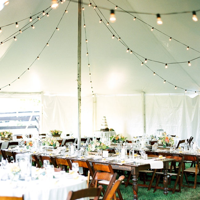 An elegant tent was set up with bistro lighting and rustic wooden decor.