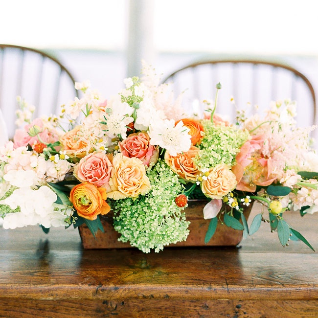Centerpieces of orange ranunculuses, peach carnations, pink roses, white stock and green lady's mantle flowers were displayed during the reception.