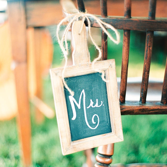 The bride and groom's reception dinner seats were designated using these simple chalkboard decorations.