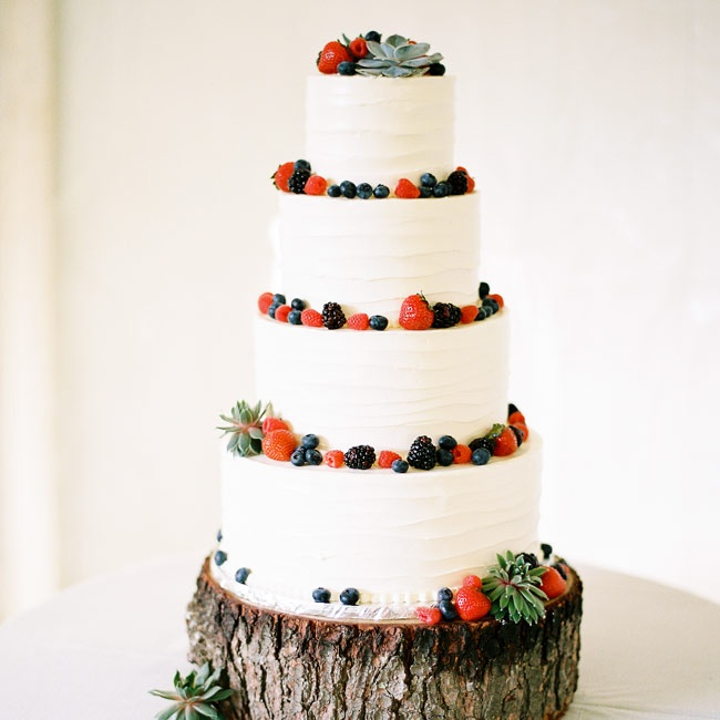 The couple's traditional white, four-tiered cake was set atop a wooden stump and topped with fresh berries and succulents.