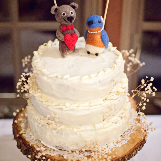 The bride's aunt, a former professional baker, created the couple's rustic ivory cake. The red velvet cake sat atop a rustic wooden cake pedestal and was adorned with dried baby's breath. A bird and bear made from wool,inspired by drawings frequently made by the couple,  topped the cake.