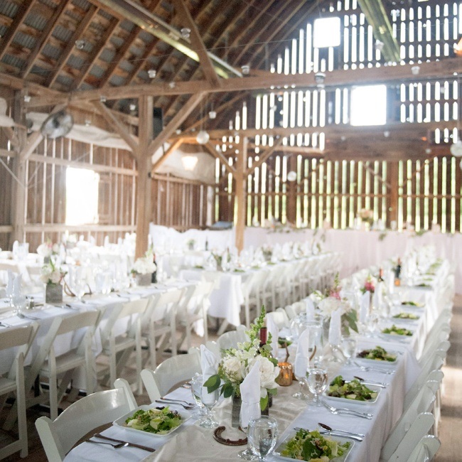 The couple transformed the rustic barn into a chic dining space with crisp white linens, simple white centerpieces and strings of votive candles hanging from the barn rafters that gave off a warm glow as the sun set.