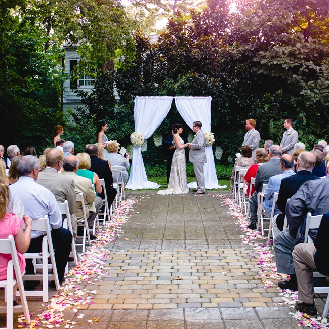 The ceremony took place in the Formal Garden at Whitehall. The intimate space was decorated with scattered rose petals and an elegant fabric-draped arch for a romantic vibe.