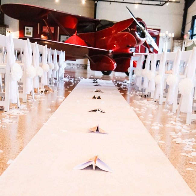 A red baron was the backdrop for the couple's aeronautical nuptials and paper airplanes lined the the ceremony aisle.
