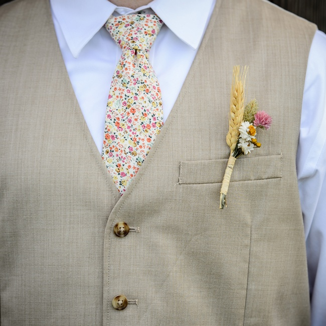 Stefan's rustic boutonniere was comprised of wheat and dried flowers. He added a hint of color to his look with a fun floral tie that picked up the pink in his boutonniere.