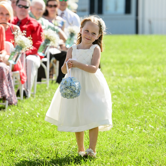 The flower girl wore an airy white summer dress as she walked down the aisle. She carried a bright blue hydrangea pomander.