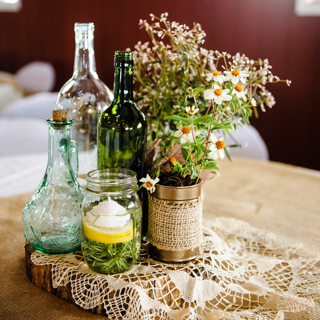Arrangements of mismatched vintage bottles and jars gave the reception decor a vintage vibe. Burlap and lace table coverings kept with the rustic country motif.