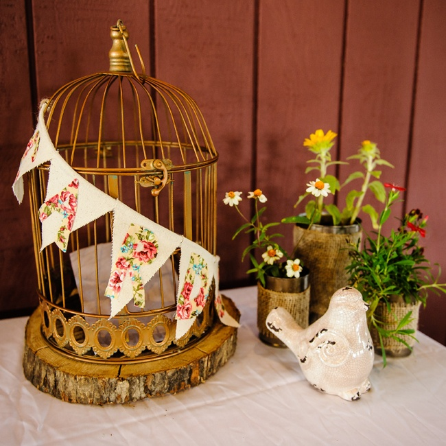 A birdcage decorated with floral bunting served as a card box for a unique, rustic touch.