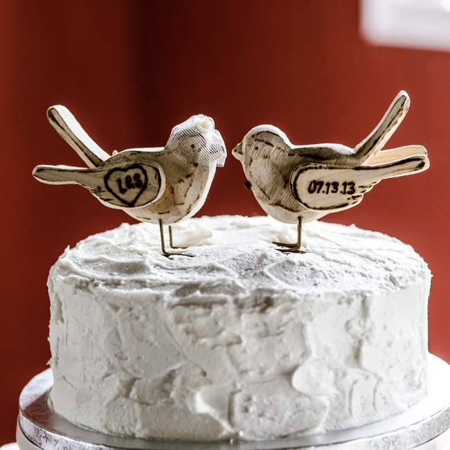 Handcarved wooden birds with the couple's initials and wedding day were perched on top of the buttercream cake.