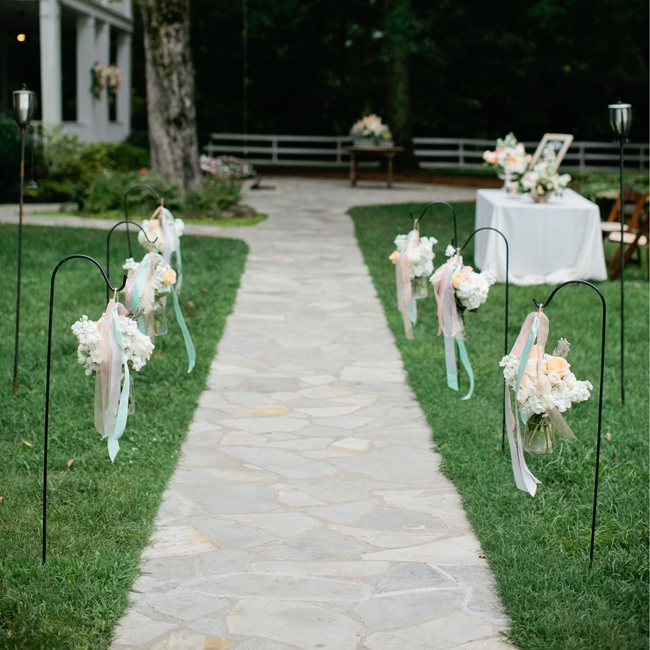Flowing organdy ribbon in a pastel color palette and simple mason jar arrangements hung from black shepard's hooks added a whimsical flair to the ceremony decor.