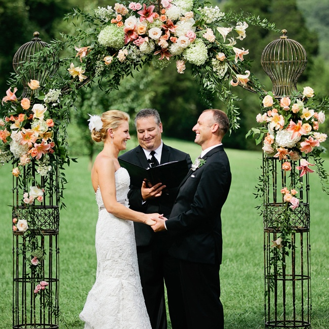 Exquisite vintage-inspired arrangements adorned an elaborate wedding arch composed of antique birdcages.