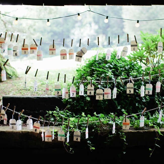 The couple used vintage gift tags for the escort cards, decorating each with colorful ribbon. For a rustic vibe, clothes pins secured each card to a string of twine.