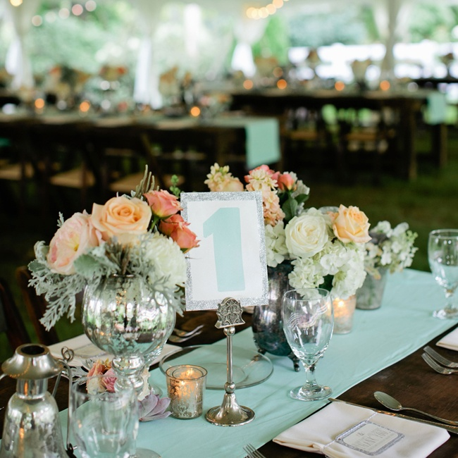 Distressed silver vessels, votive candles and peachy pink roses gave off a romantic 1920's style elegance.