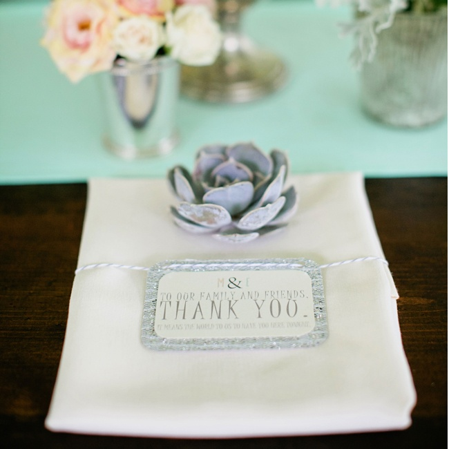 Miniature gray succulents adorned the simple ivory linens.