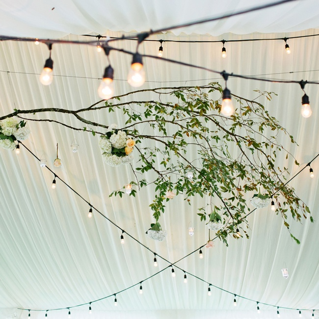 Bistro lights and glass votive candle holders illuminated the reception tent's fabric draped ceiling.