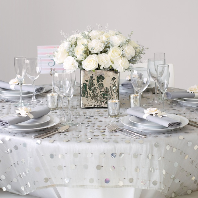 If you're on a limited budget, choose luxe details on a smaller scale to get the look you want. Start with your basics: round table, simple chairs and one centerpiece; then add big impact upgrades. Linens get pricey, so consider a sheet overlay on half your tables for that wow-factor.