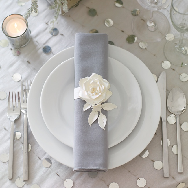 A paper flower napkin ring dresses up a simple place setting.
