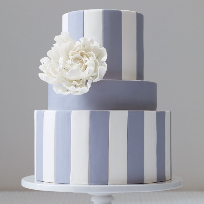 One large sugar flower tops this three-tier fondant cake instead of a cascade of flowers.