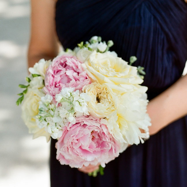 Pale pink peonies mixed with ivory roses and white delphiniums in the bridesmaids' bouquets for a pop of color.