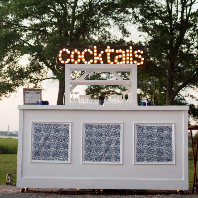 A modern bar with fun marquee lighting from 428 Main Vintage Rentals was set up outside for guests. The bar was decorated with navy damask fabric that matched their invitations and reception table settings.