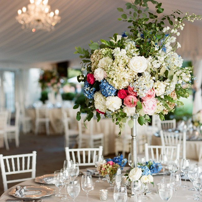Extravagant high centerpieces filled with hydrangeas, roses, peonies and lily of the valley gave the reception tables an English garden party feel.